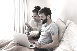 Young couple watching movie on laptop computer while sitting on a bed