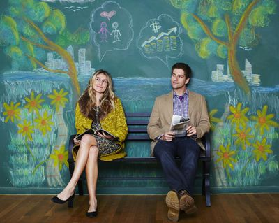 A man and woman sitting on a park bench with a depiction of financial goals