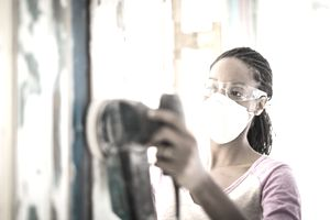 A woman wears a facemask and goggles while sanding a wall with an electric sander