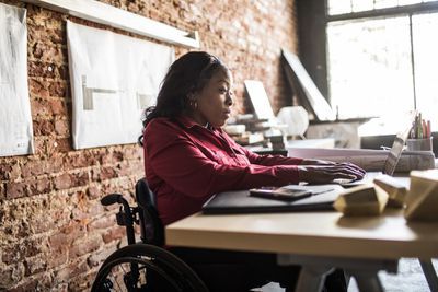 Woman in a wheelchair working on a laptop