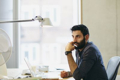 A man sits in front of a computer thinking seriously about his investments