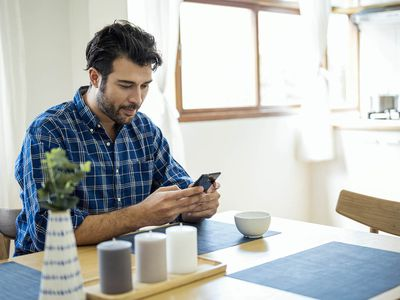 A Man using smartphone while sitting at dining table
