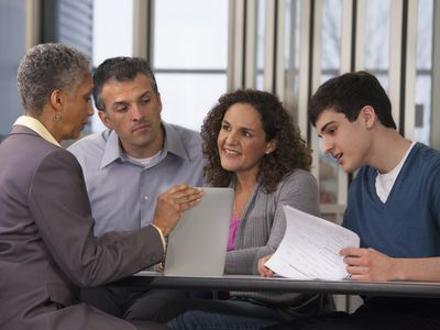 Parents and son talking with a banker as they open a savings account.