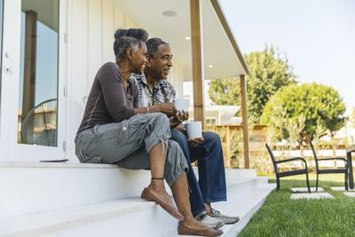 A retired couple enjoy a cup of coffee on their porch.