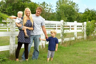 Young family standing by a white fence