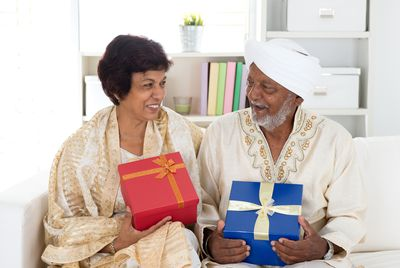 Portrait of senior Indian couple sitting at sofa with gift box smiling happily. Indian family living lifestyle at home.
