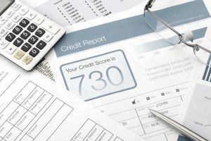 Credit report form on a desk with calculator and other paperwork.