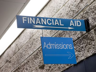 financial aid and admissions signs hand on a concret block wall point the direction to go