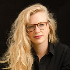 Headshot of a blonde woman with glasses on a black background.
