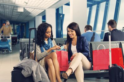 Two women in an airport look at items in their shopping bags.