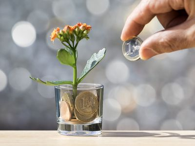 Fingers of a man with a currency of Euro, paying a plant that grows with coins of the euro-zone