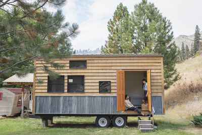 Young couple talking in doorway of their tiny house.