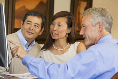 Couple looking at computer screen with their financial advisor