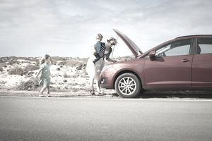 Woman checking engine of broken-down car.