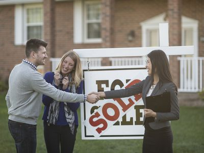 Couple in front of sold home