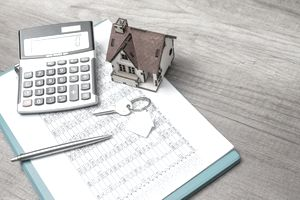 Mortgage underwriting calculation sheet on a clipboard and a model house sitting on top of the sheet.