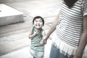 A young girl smiles up at the woman whose hand she is holding.