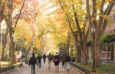 students with backpacks walking on the campus of University of Pennsylvania during the fall