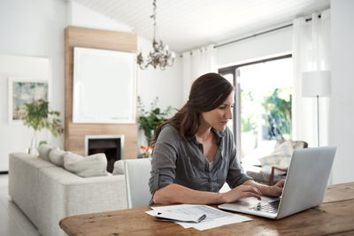 person in grey shirt sitting at kitchen table on computer