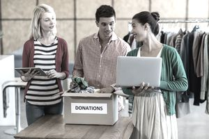 Two women and a man look at a tablet and laptop while standing near a donations box