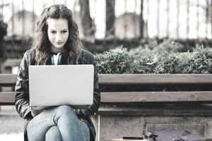 Student studying on a laptop in the garden of the university