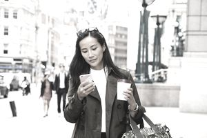 Businesswoman looks at smart phone while walking in city