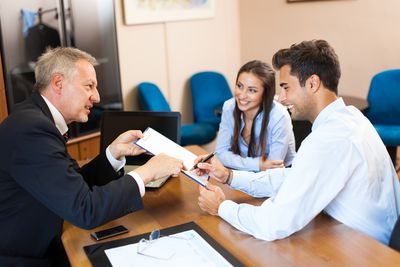 Young couple signing contract a home purchase contract with their agent