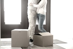 Below-the-Neck Shot of Man and Woman Embracing in the Doorway of a House With Moving Boxes Around Them