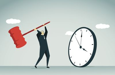 A man smashes a clock with a mallet
