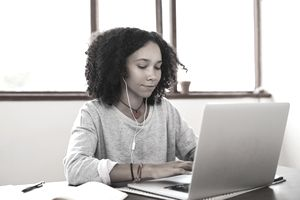 young girl working on computer with headphones in
