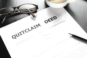 Quitclaim deed form on table with reading glasses, pen, and coffee mug