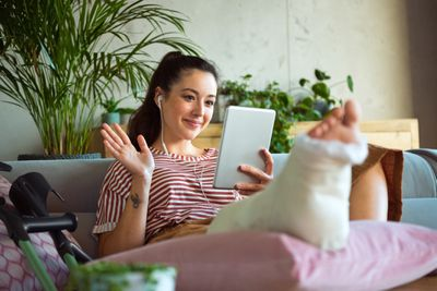 A girl sits on a couch with her broken leg propped up on a pillow, holding an ipad and waving to someone on a video call