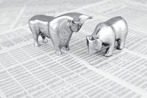 Small silver figurines of a bull and a bear sit on top of a printed stock market report