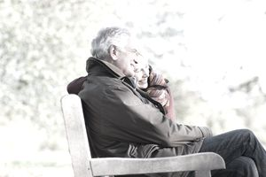 Senior couple hugging in park bench