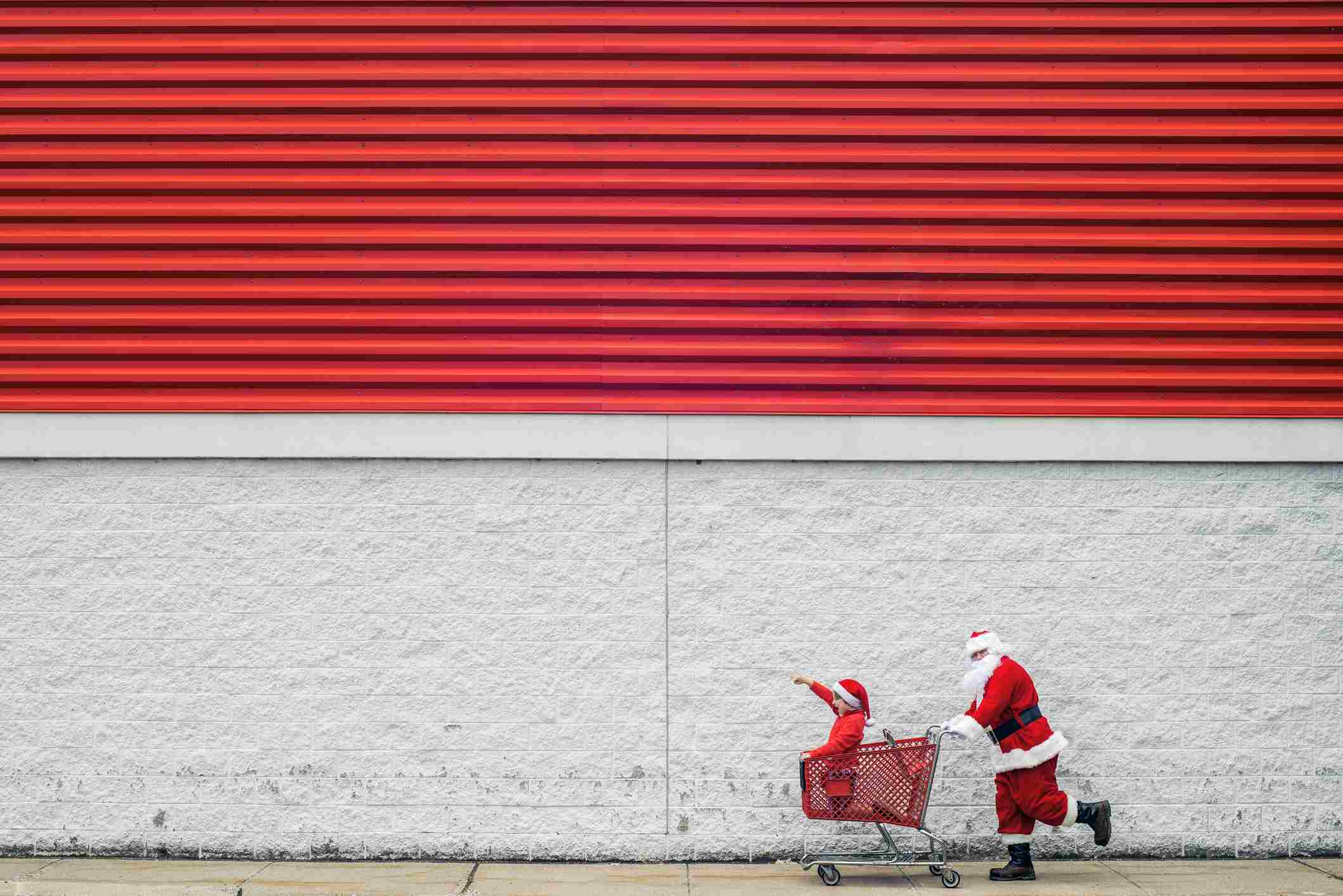 Man in a Santa costume pushing a child in a shopping cart in a rush to buy gifts