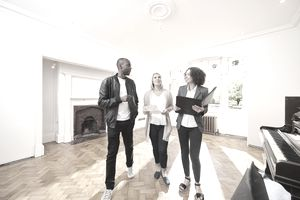 an estate agent shows a couple around a refurbished period home
