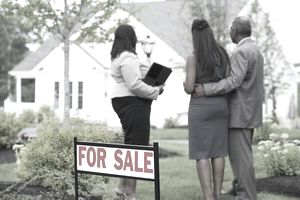 Real estate agent showing a house for sale to a couple