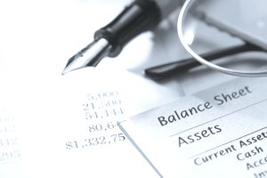 Close-up of balance sheet with pen and eyeglasses