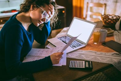A woman sits at a table researching how to build credit