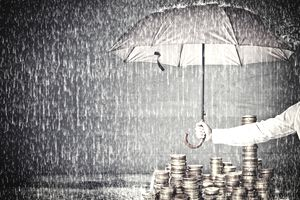 Man holding an umbrella over a stack of coins to give protection of assets from rain