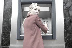 Woman carefully using debit card at ATM