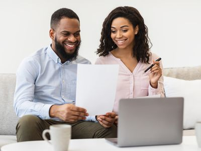 A young couple reviews a document while sitting on a couch in front of laptop