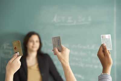 Three students raise their hands, each grasping a credit card, while in the background, a teacher standing before a blackboard looks on with a bemused expression.