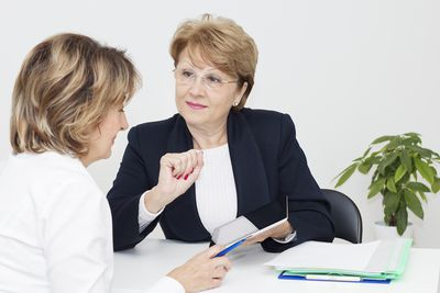 Two women seated at a white table reviewing contracts