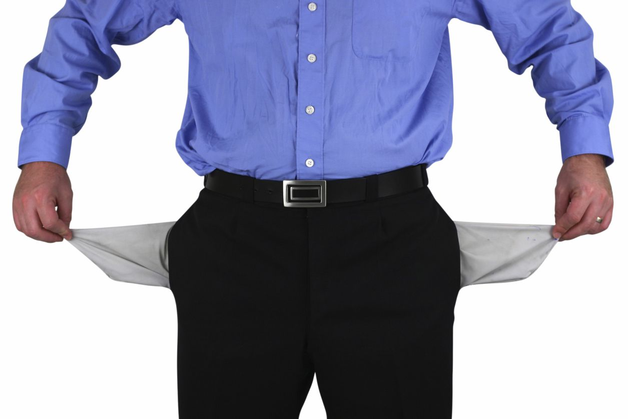man pulls both side pockes of his pants out showing they are empty