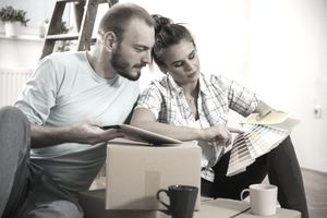 Candid shot of happy young couple sitting on the floor among boxes they moved in and looking at color swatches and talking about home improvements.