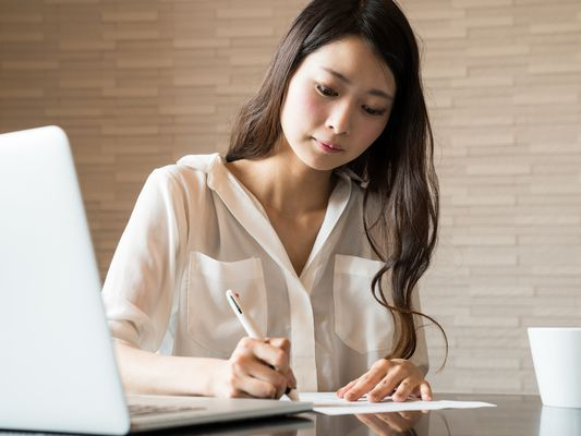Woman at a table in front of a laptop, filling out paperwork