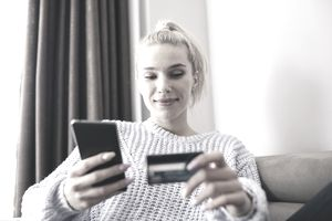 blond woman in purple sweater with credit card and phone in hands