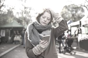 Red haired woman looking at her smartphone with her hand on her head.