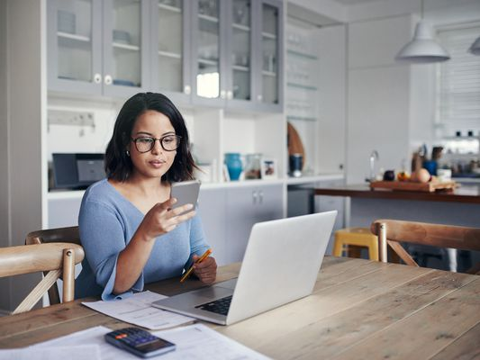 Shot of a young woman using a mobile phone and laptop while working from home